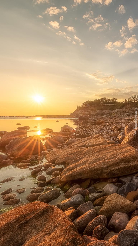 Kamienisty brzeg morza w promieniach słońca