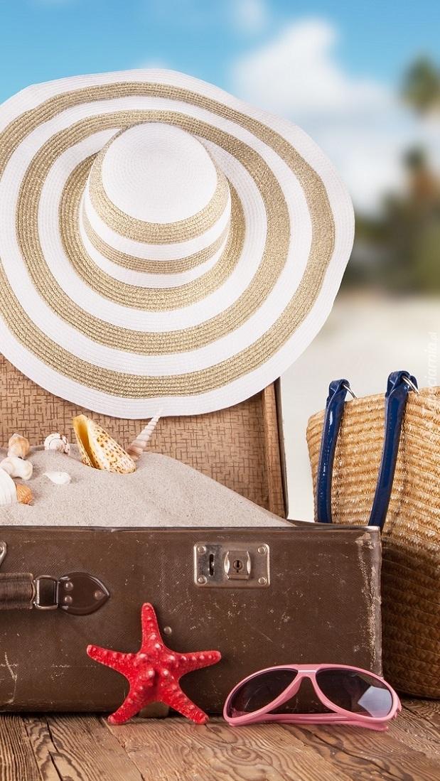Kapelusz na walizce z piaskiem i muszelkami