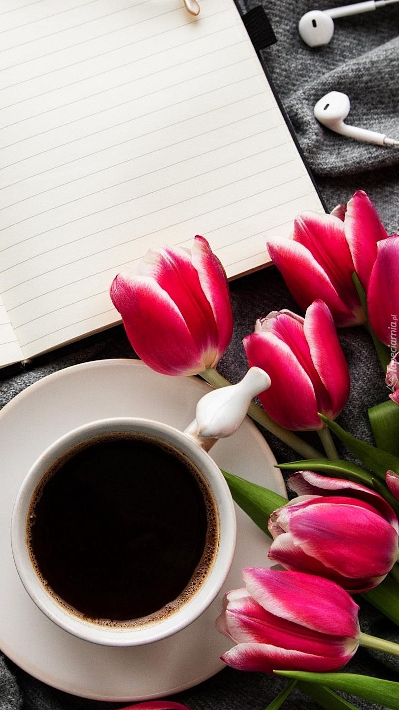 Kawa obok tulipanów i zeszytu