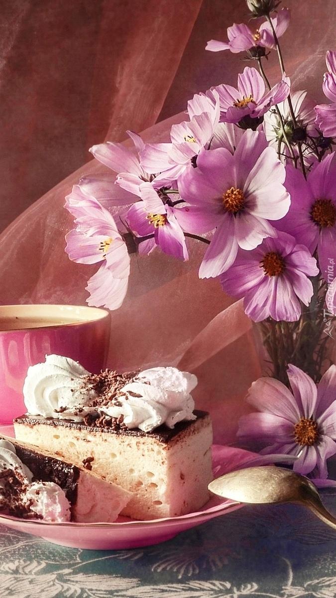 Kawałek ciasta obok różowej kosmei w wazonie