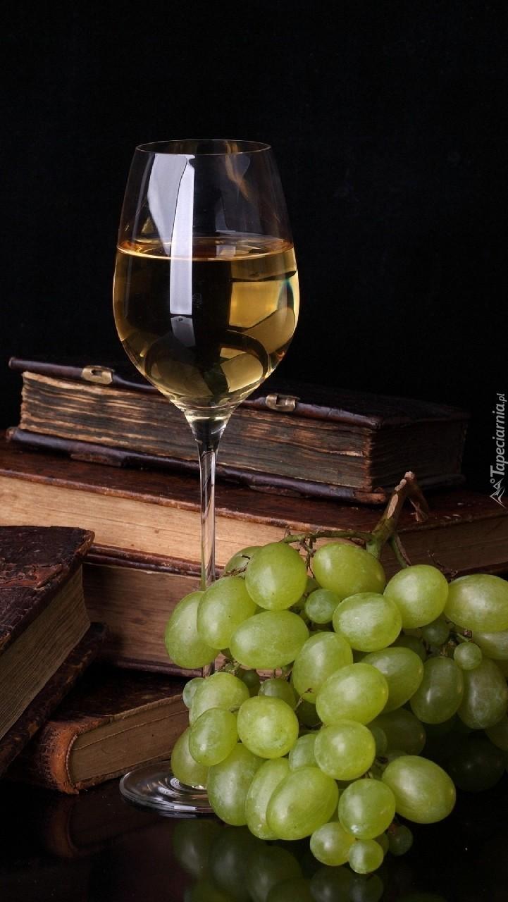 Kieliszek białego wina obok stosu książek
