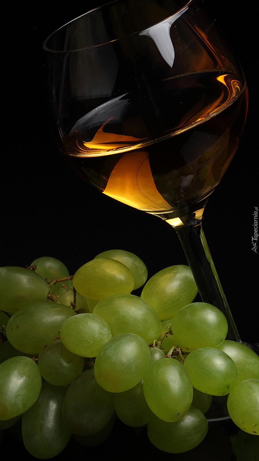 Kieliszek wina obok winogron