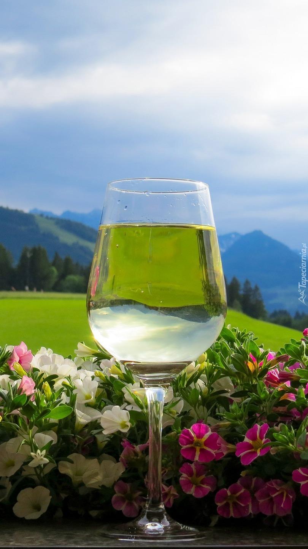 Kieliszek z winem pośród kwiatów