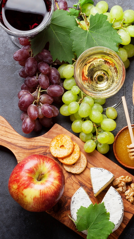 Kieliszki z winem obok winogron i deski z serem