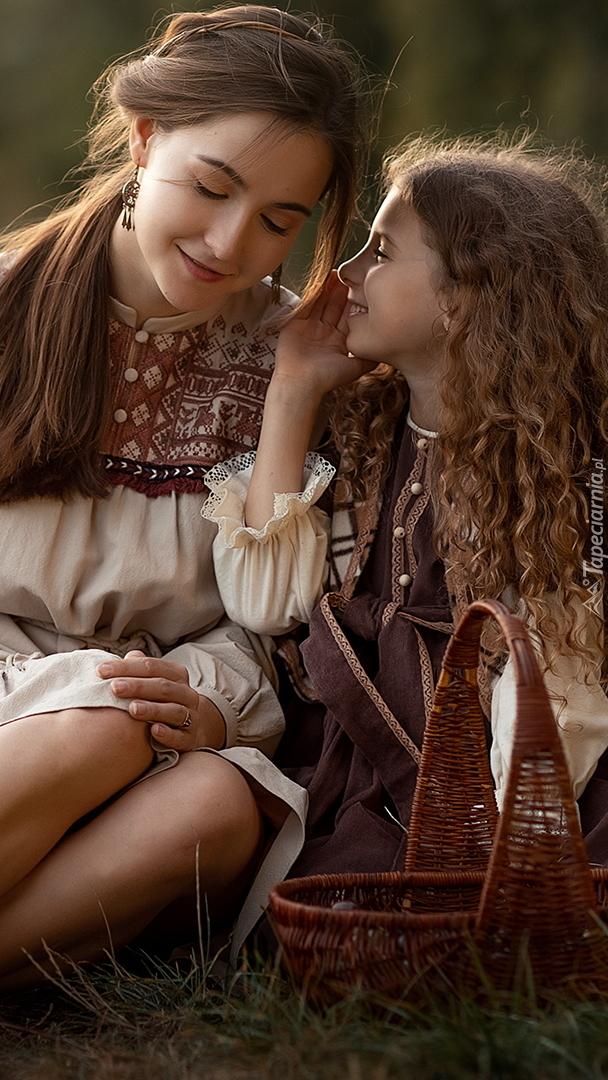 Kobieta i dziewczynka siedzące na trawie