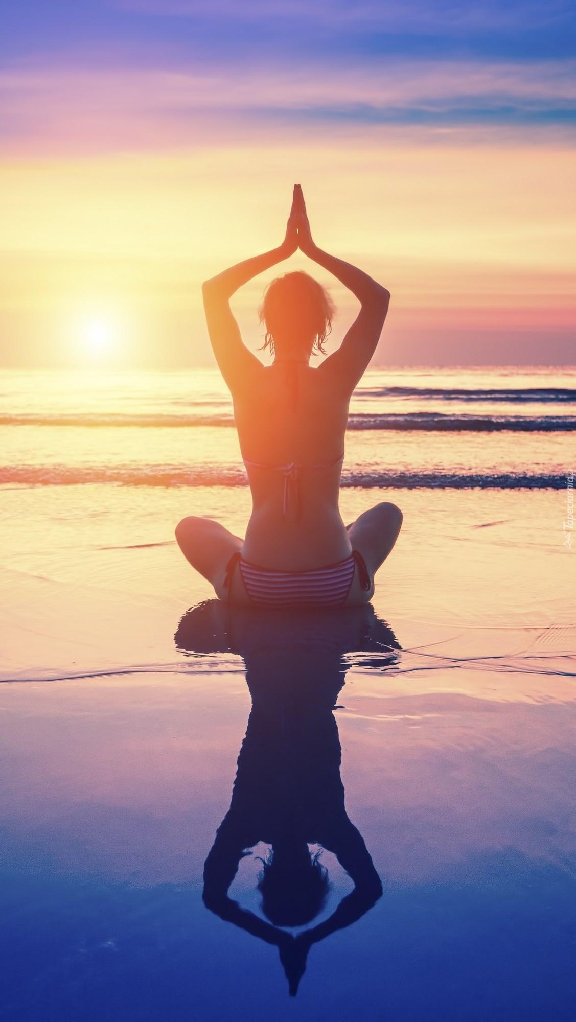 Kobieta medytująca na plaży