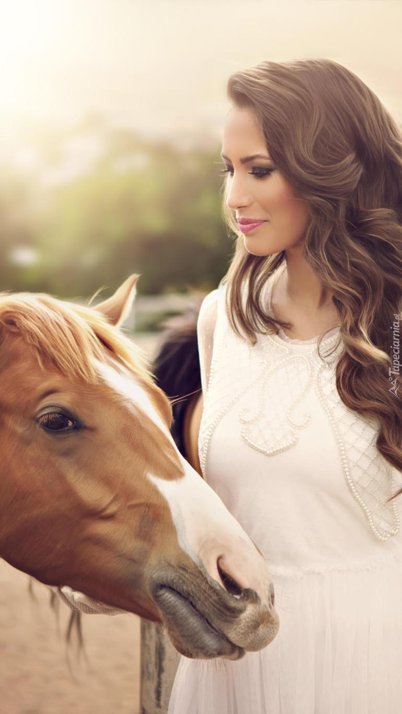 Kobieta obok gniadego konia