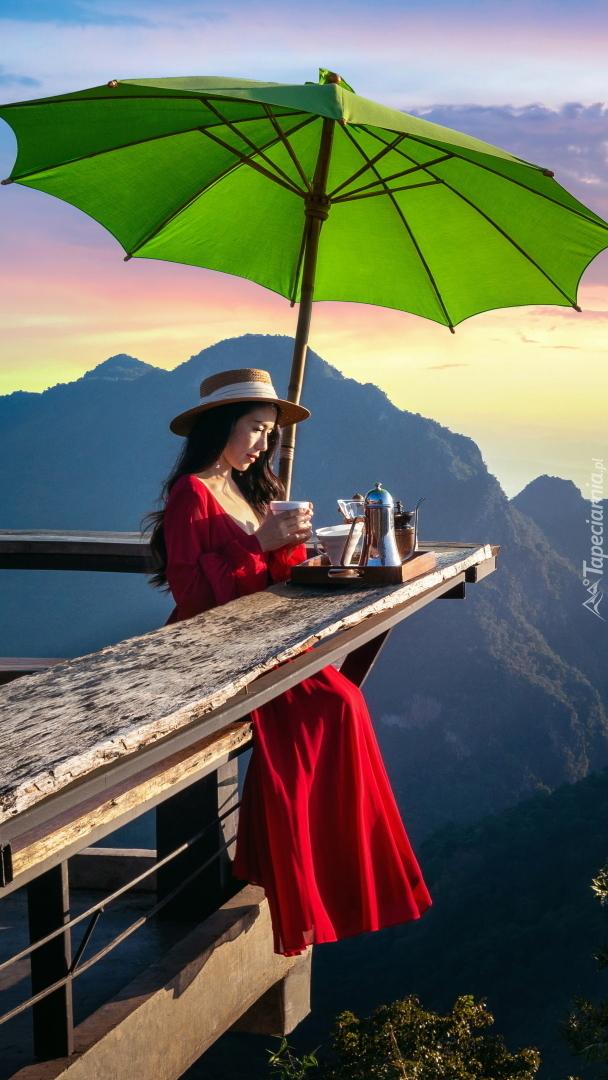 Kobieta pijąca kawę na tarasie widokowym