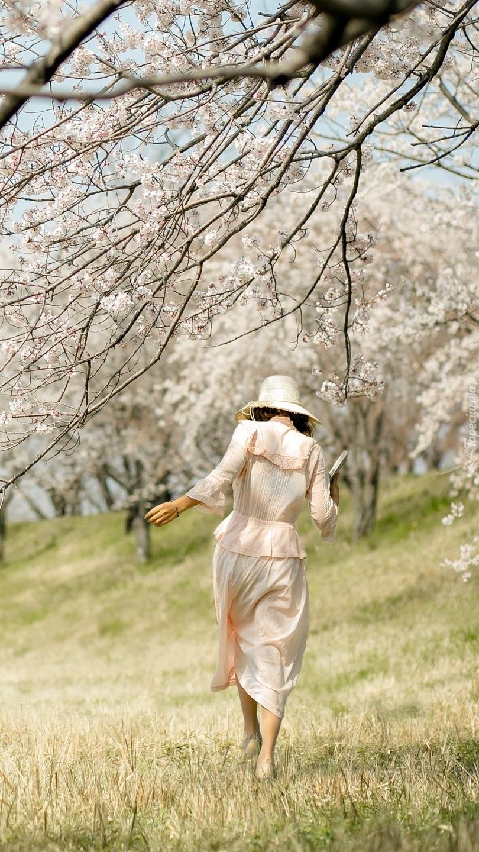 Kobieta pod kwitnącym drzewem