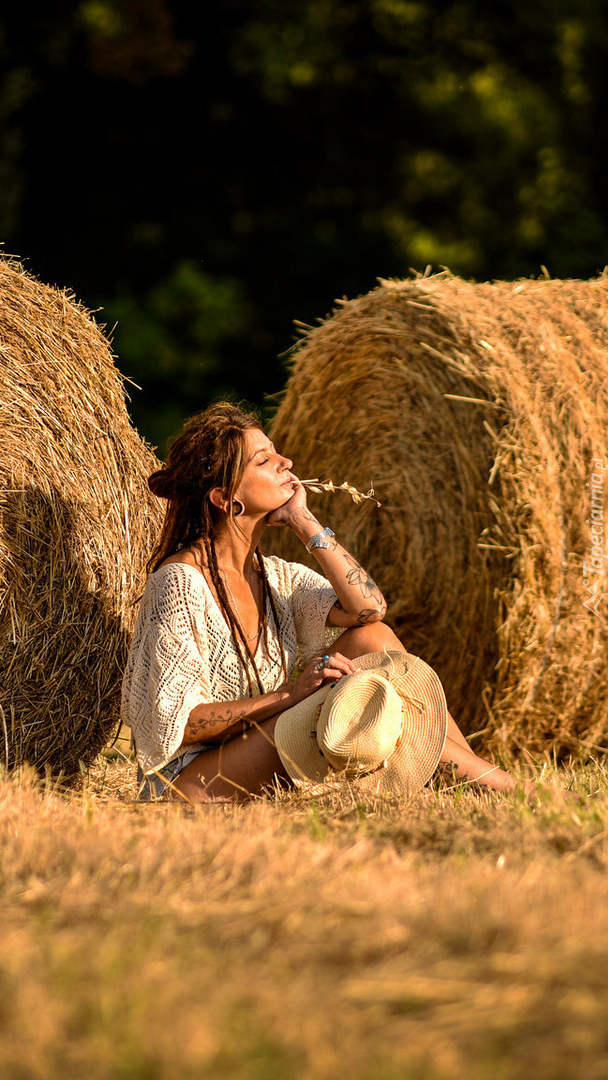Kobieta przy belach siana
