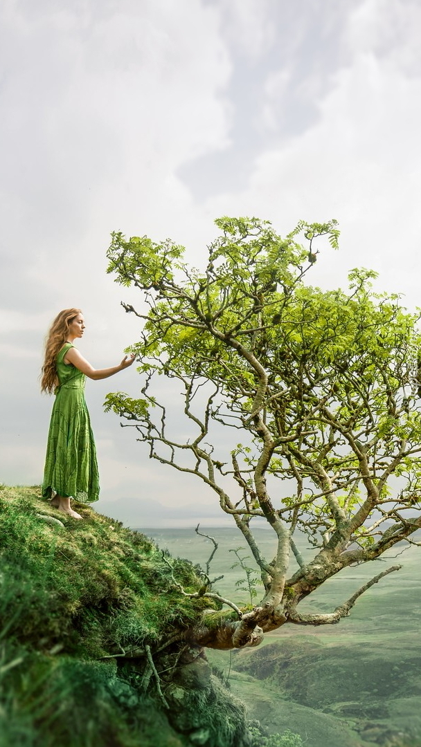 Kobieta przy drzewie na skarpie