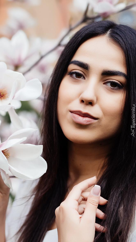 Kobieta przy krzewie magnolii