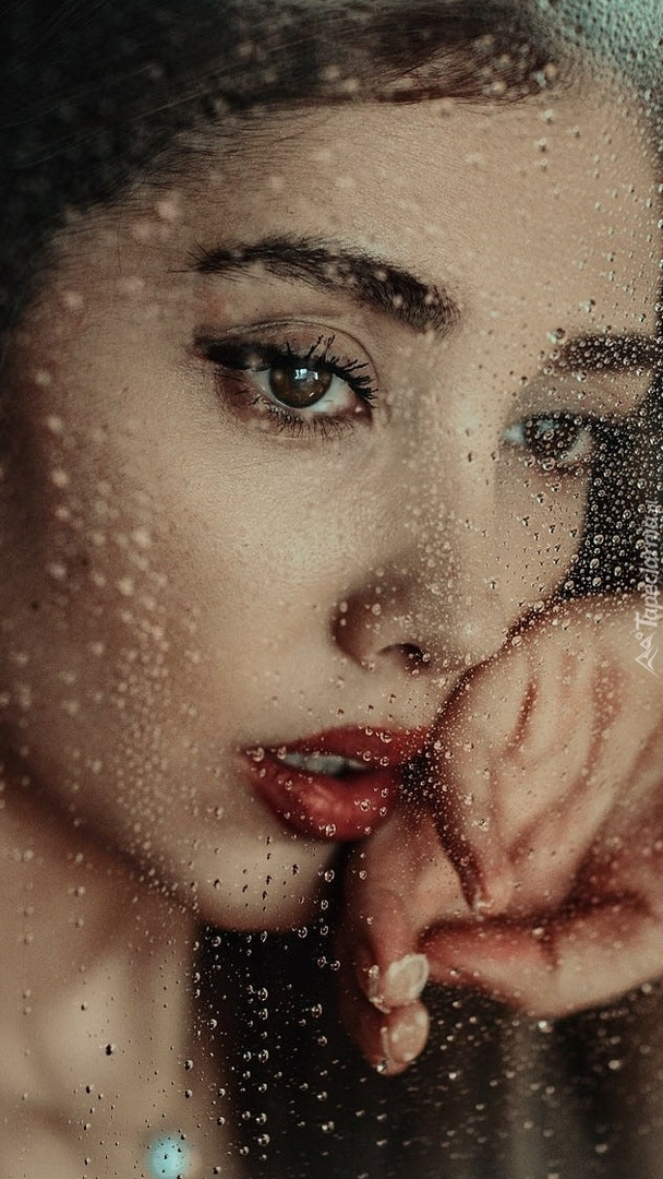 Kobieta przy mokrej szybie