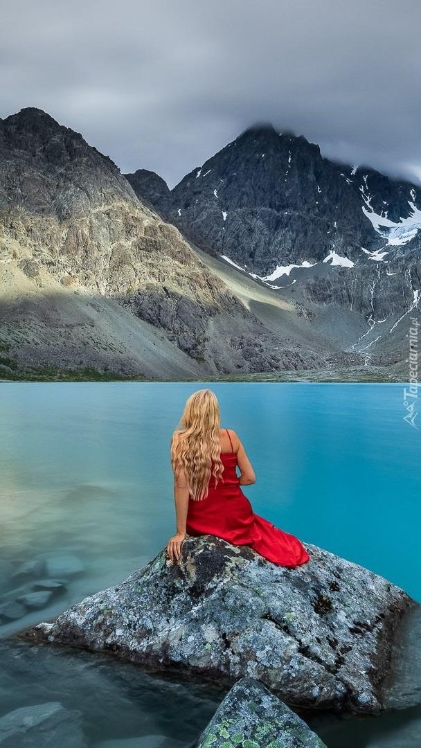 Kobieta siedząca na kamieniu w jeziorze