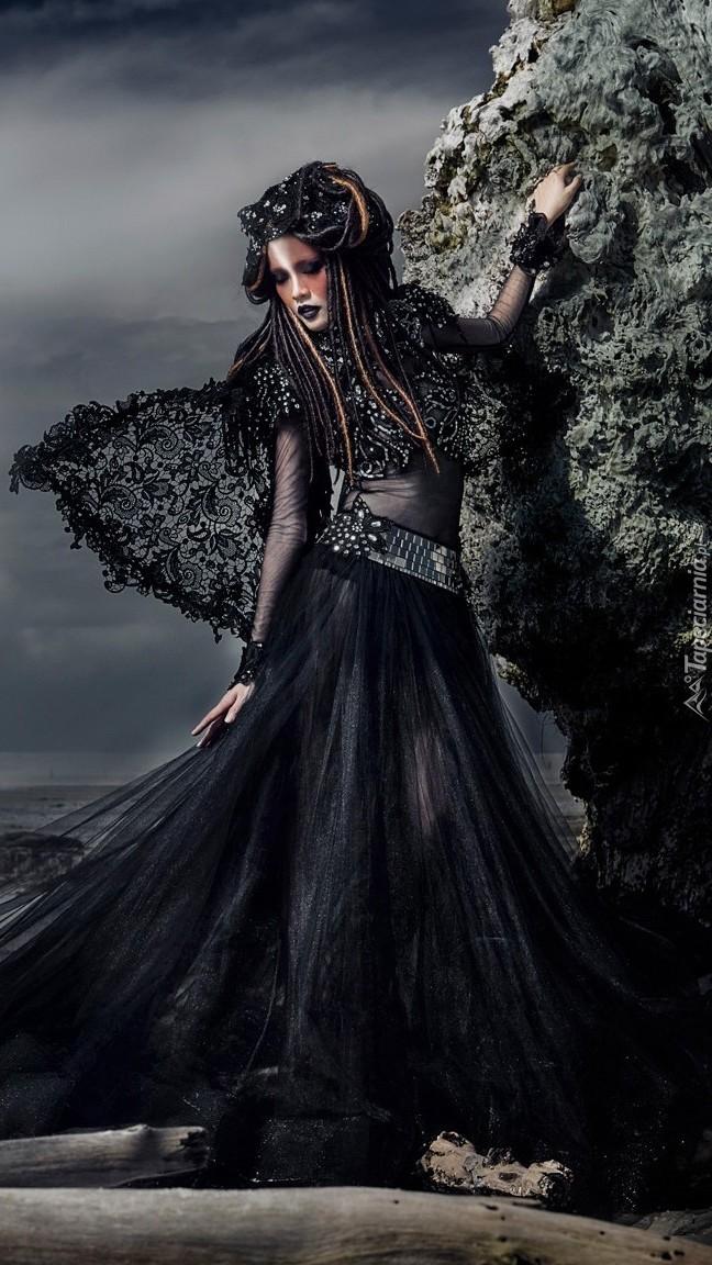 Kobieta w czarnej sukni stoi przy skałach