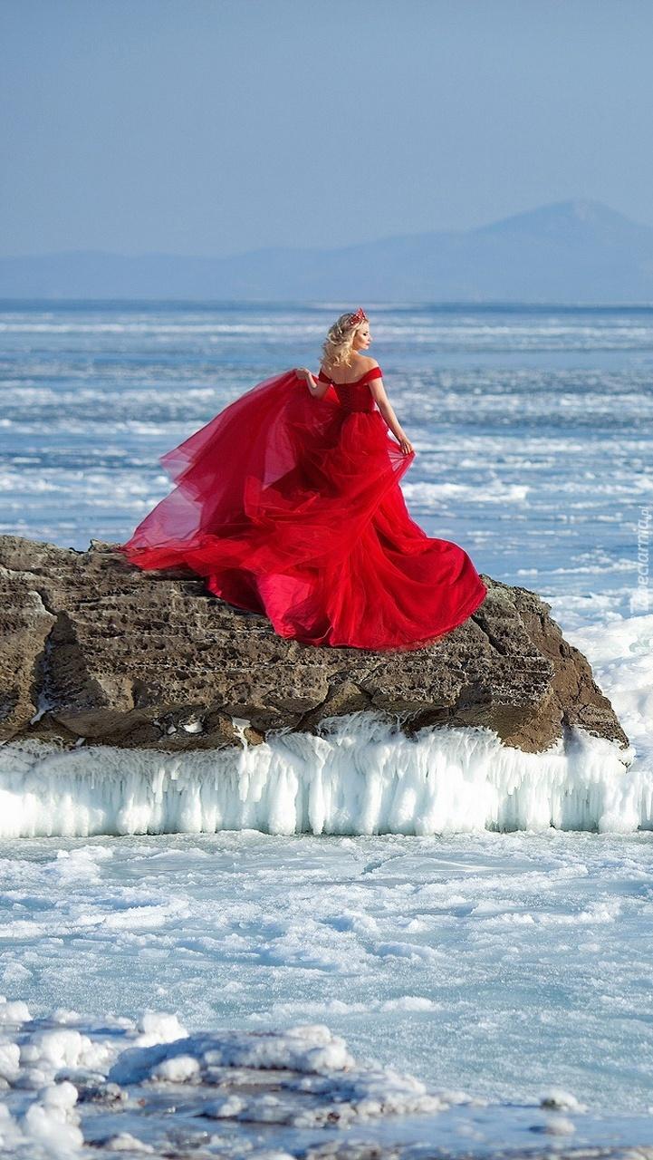 Kobieta w czerwonej sukni na skałach