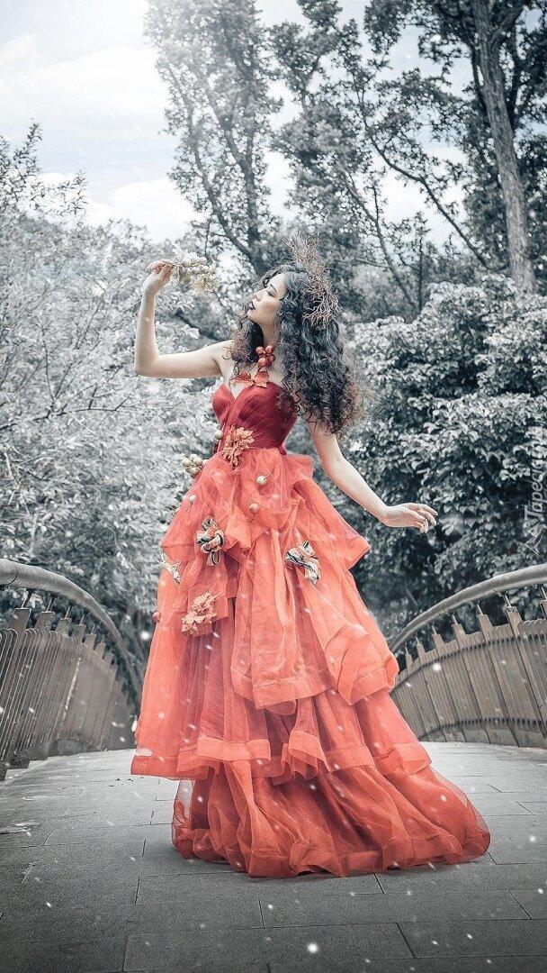 Kobieta w długiej sukni na moście