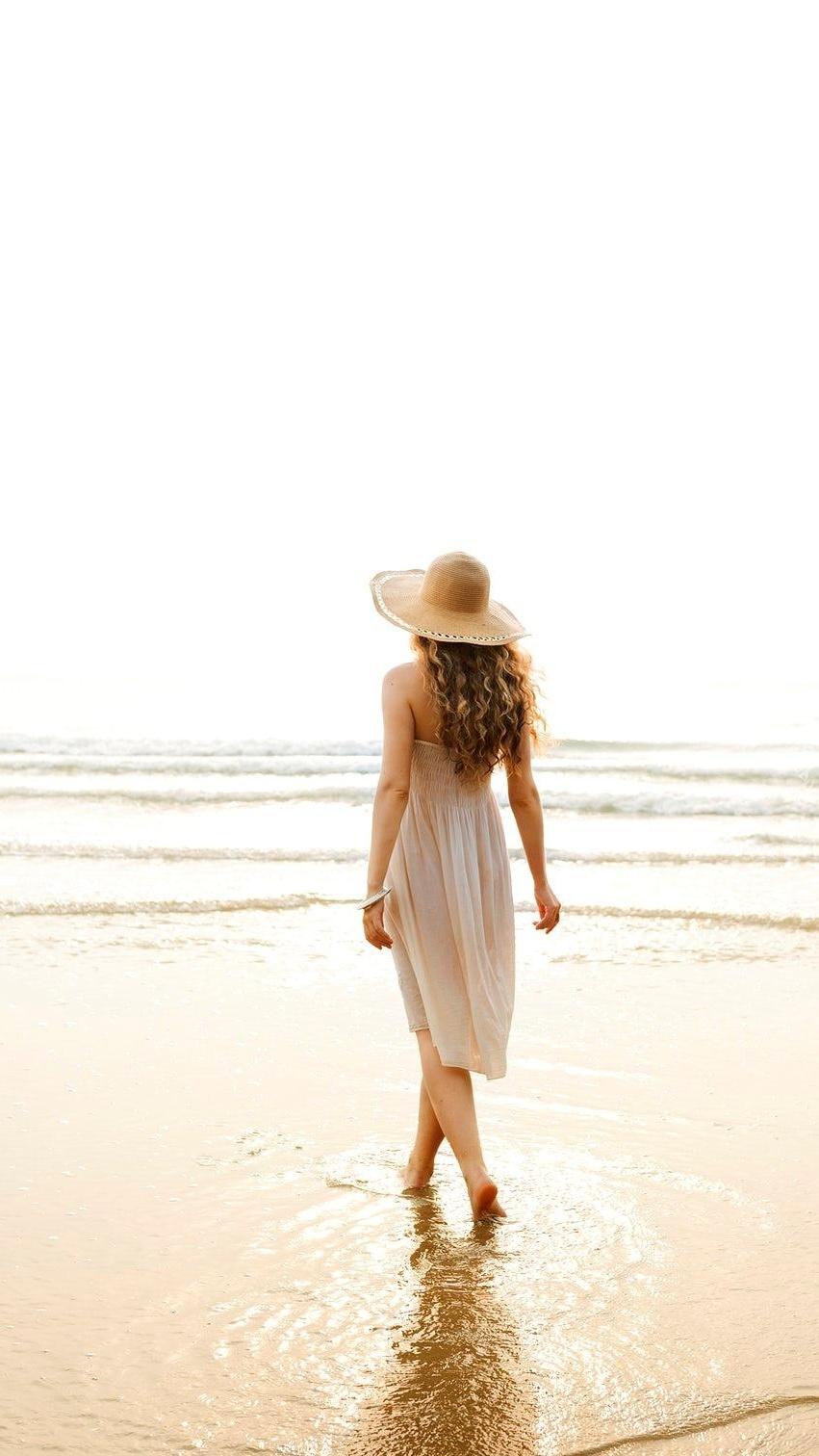 Kobieta w kapeluszu na brzegu morza