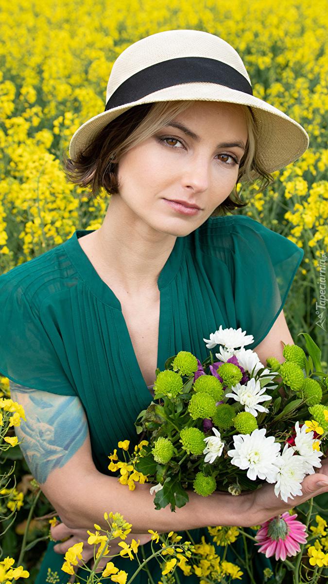 Kobieta w kapeluszu z bukietem kwiatów