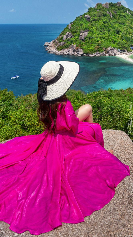 Kobieta w różowej sukni na skale nad morzem