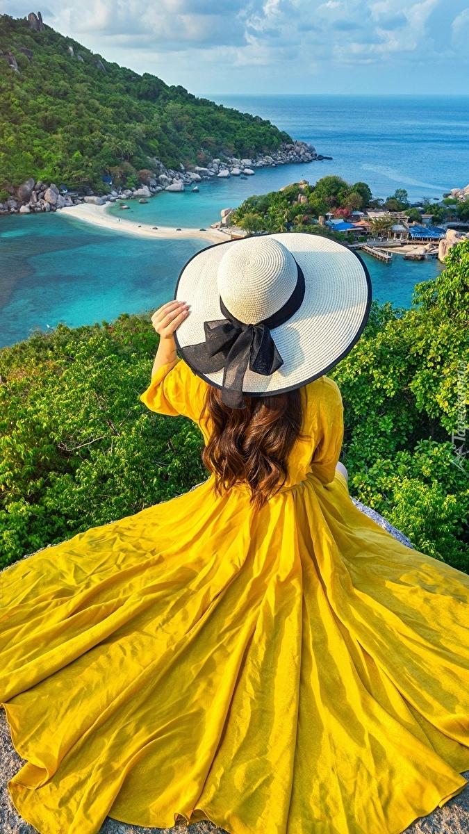 Kobieta w żółtej sukience na skale