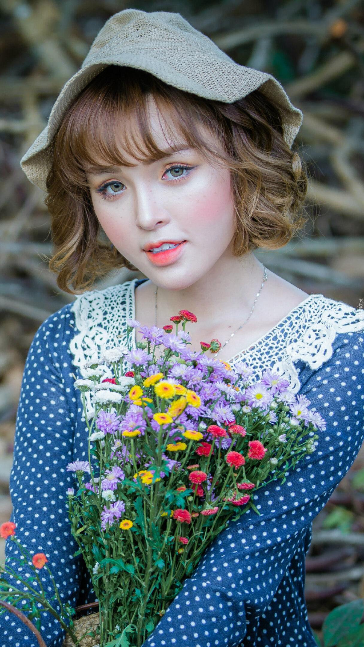 Dziewczyna z bukietem kwiatów na łące