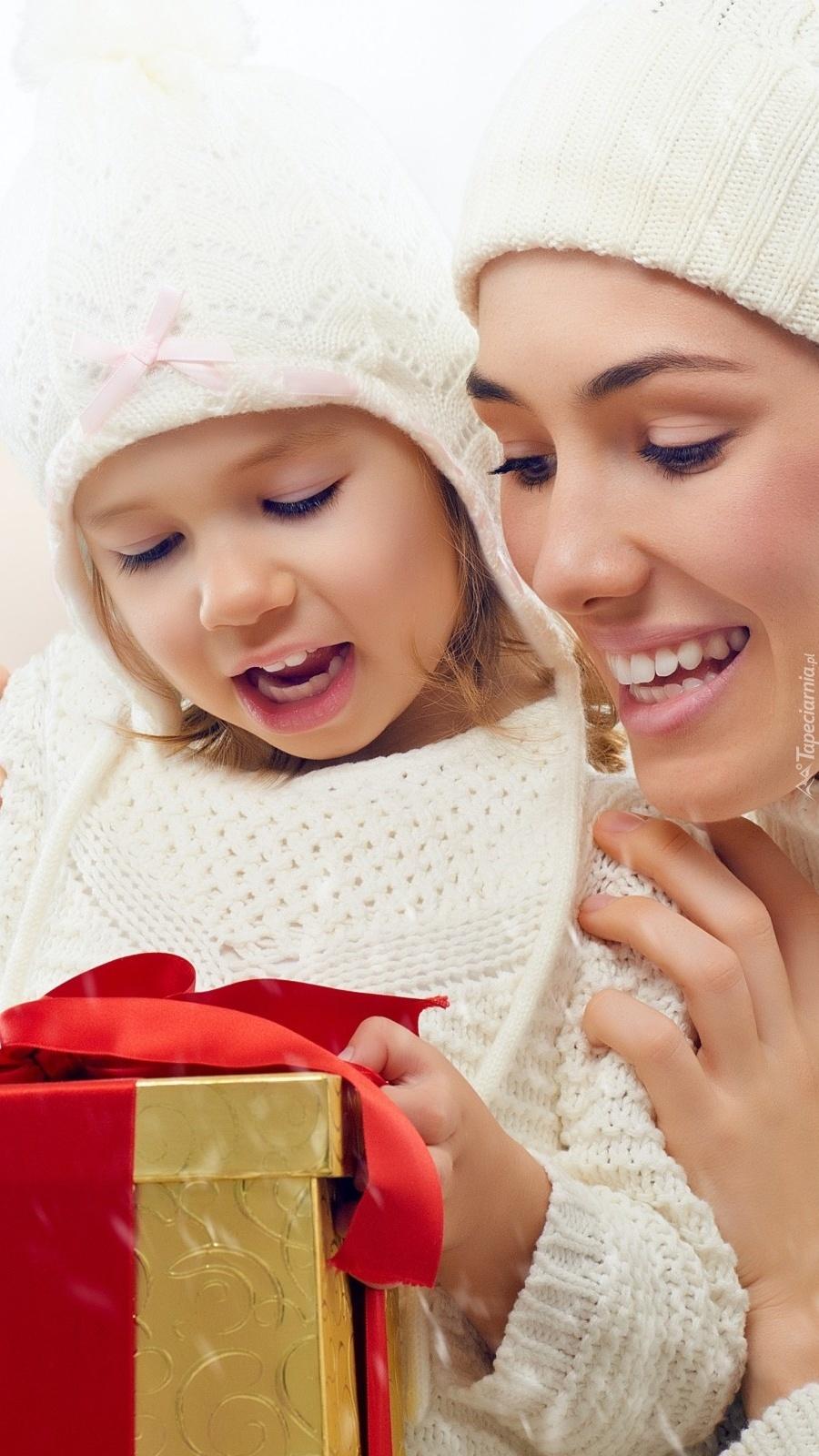 Kobieta z dzieckiem otwierają prezent