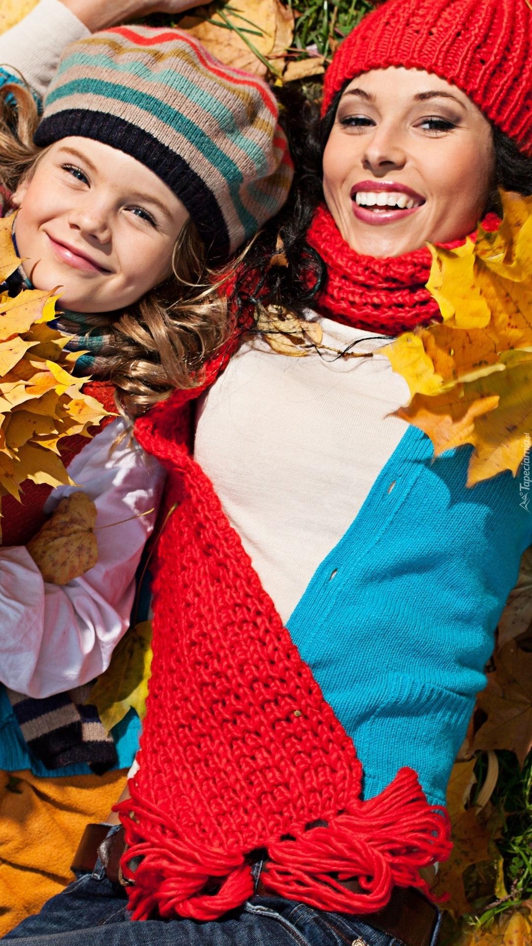 Kobieta z dziewczynką w jesiennych liściach