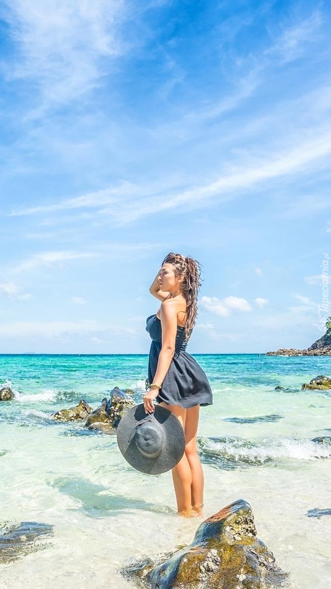 Kobieta z kapeluszem na brzegu morza