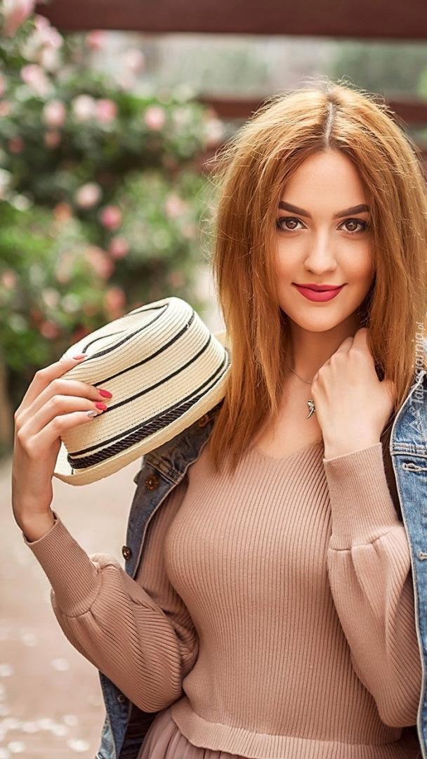 Kobieta z kapeluszem w ręce