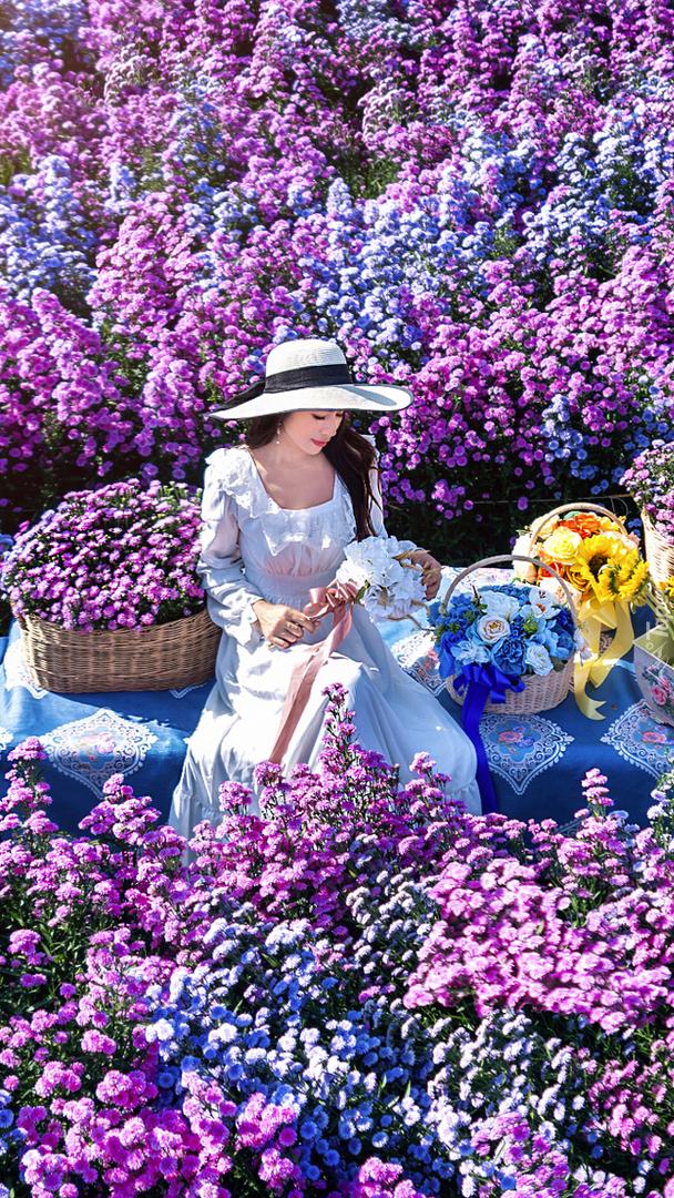 Kobieta z koszykami na stole wśród kwiatów