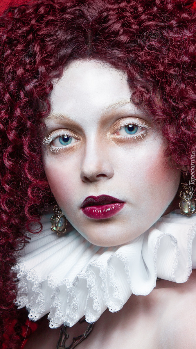 Kobieta z kręconymi bordowymi włosami