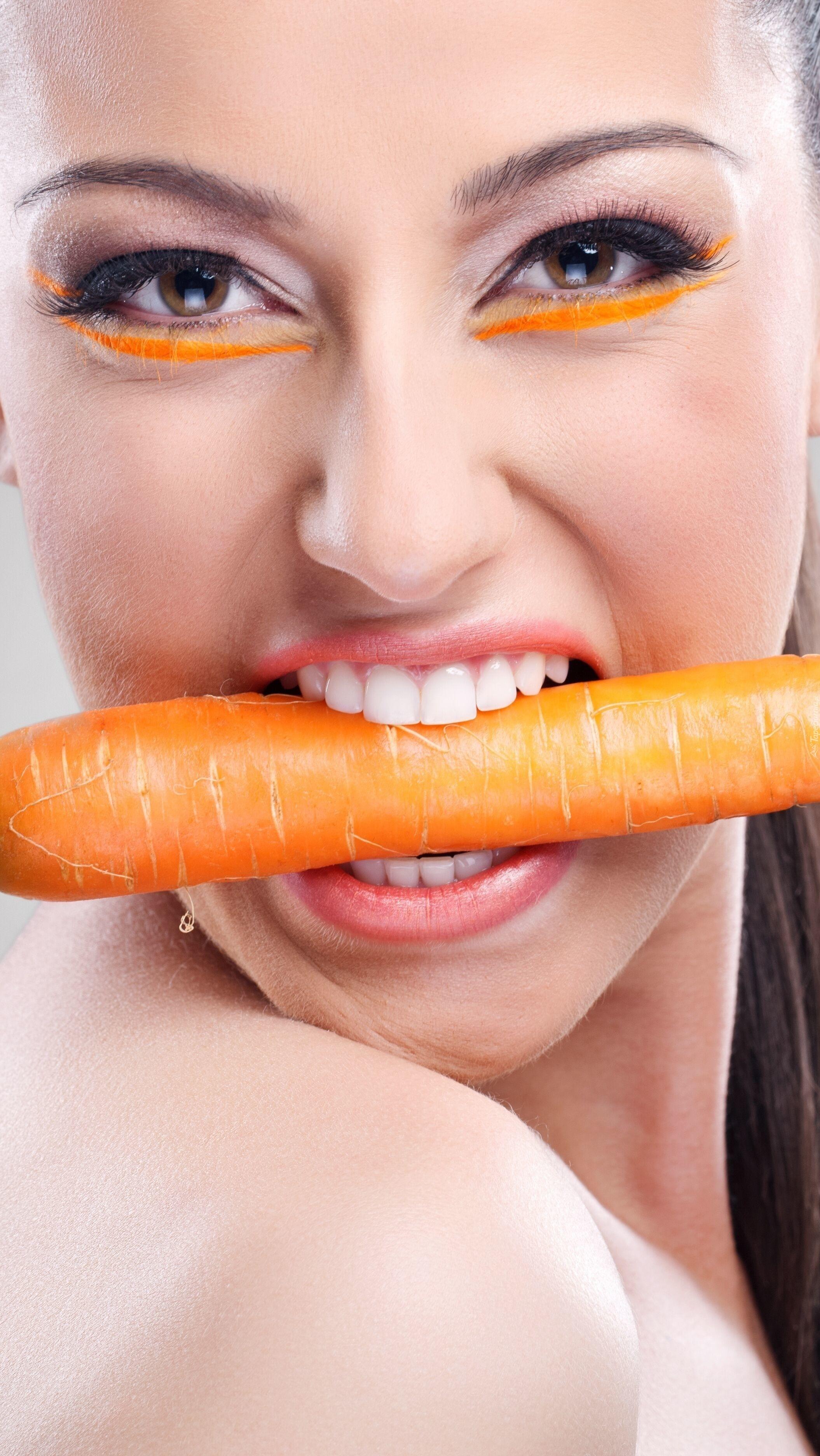 Kobieta z marchewką w zębach