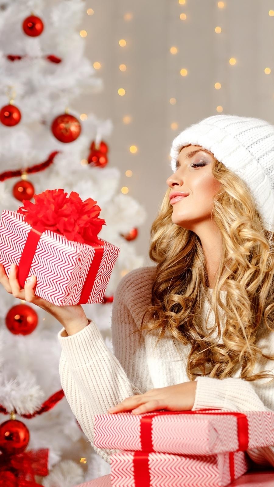 Kobieta z prezentami przy choince