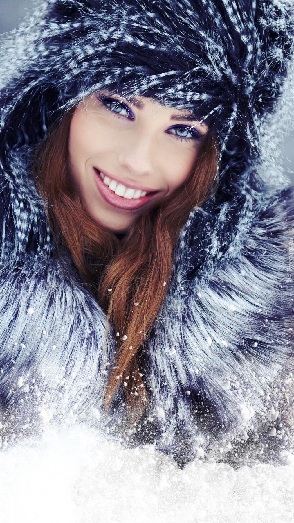 Kobieta z uśmiechem na twarzy w zimowej czapce