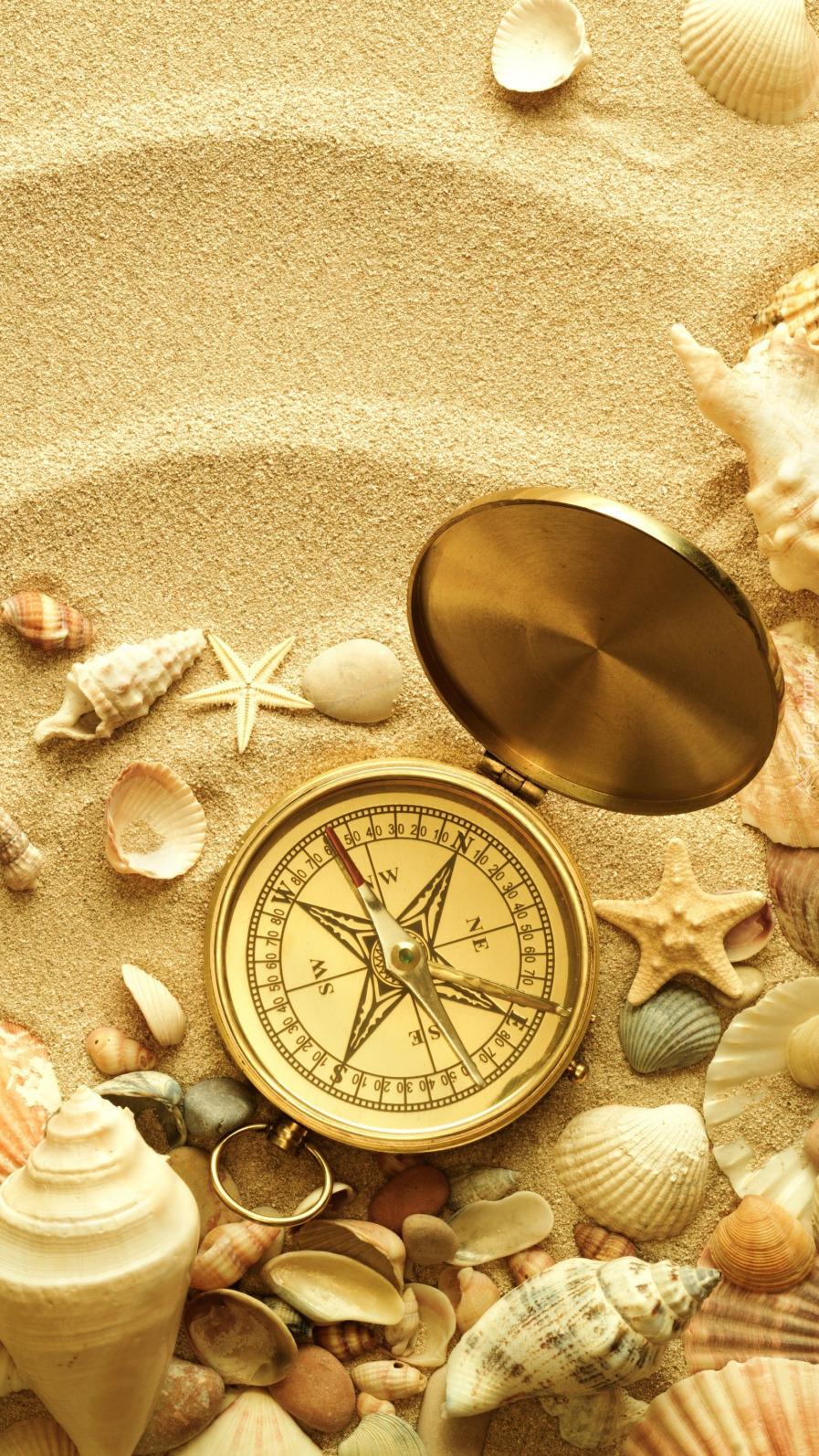 Kompas i muszelki na piasku