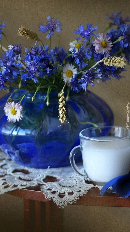 Kompozycja z polnych chabrów i stokrotek w wazonie z kubeczkiem mleka