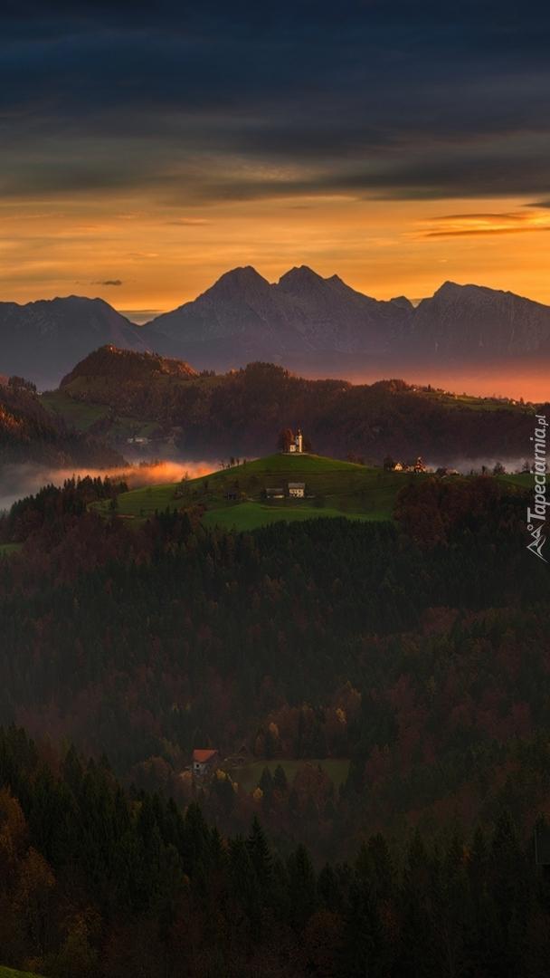 Kościół i domki na tle Alp Julijskich