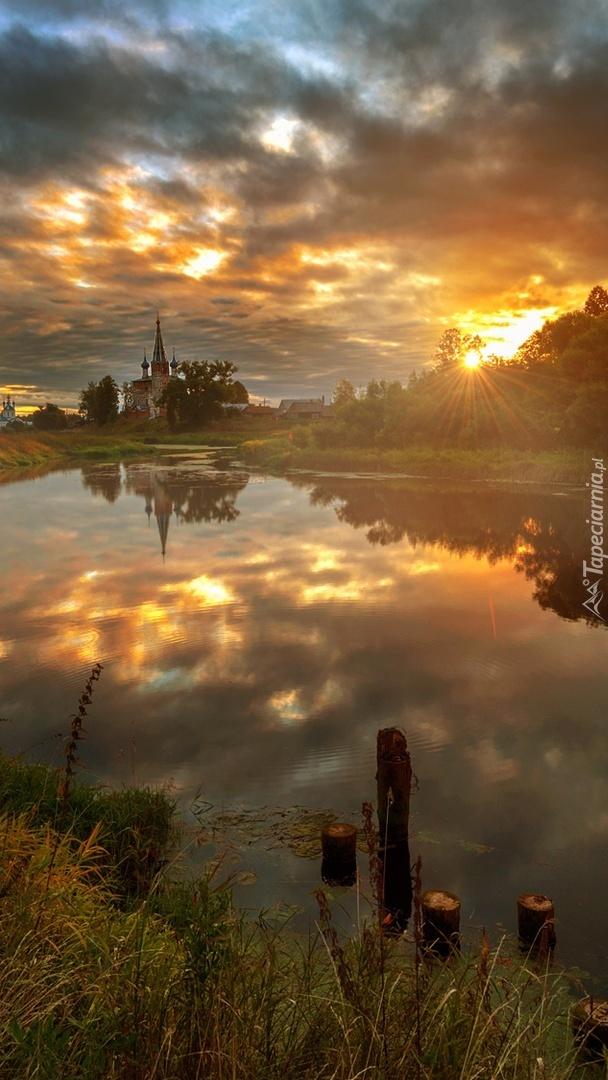 Kościół nad rzeką w promieniach słońca