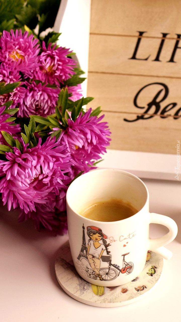 Kubek kawy obok astrów
