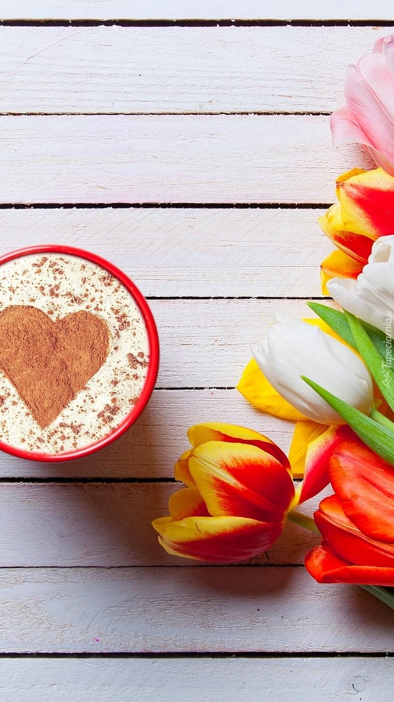Kubek kawy obok tulipanów