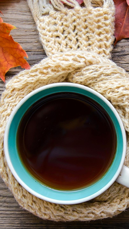 Kubek kawy owinięty szalikiem