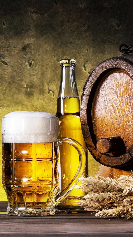 Kufel piwa obok butelki i beczki