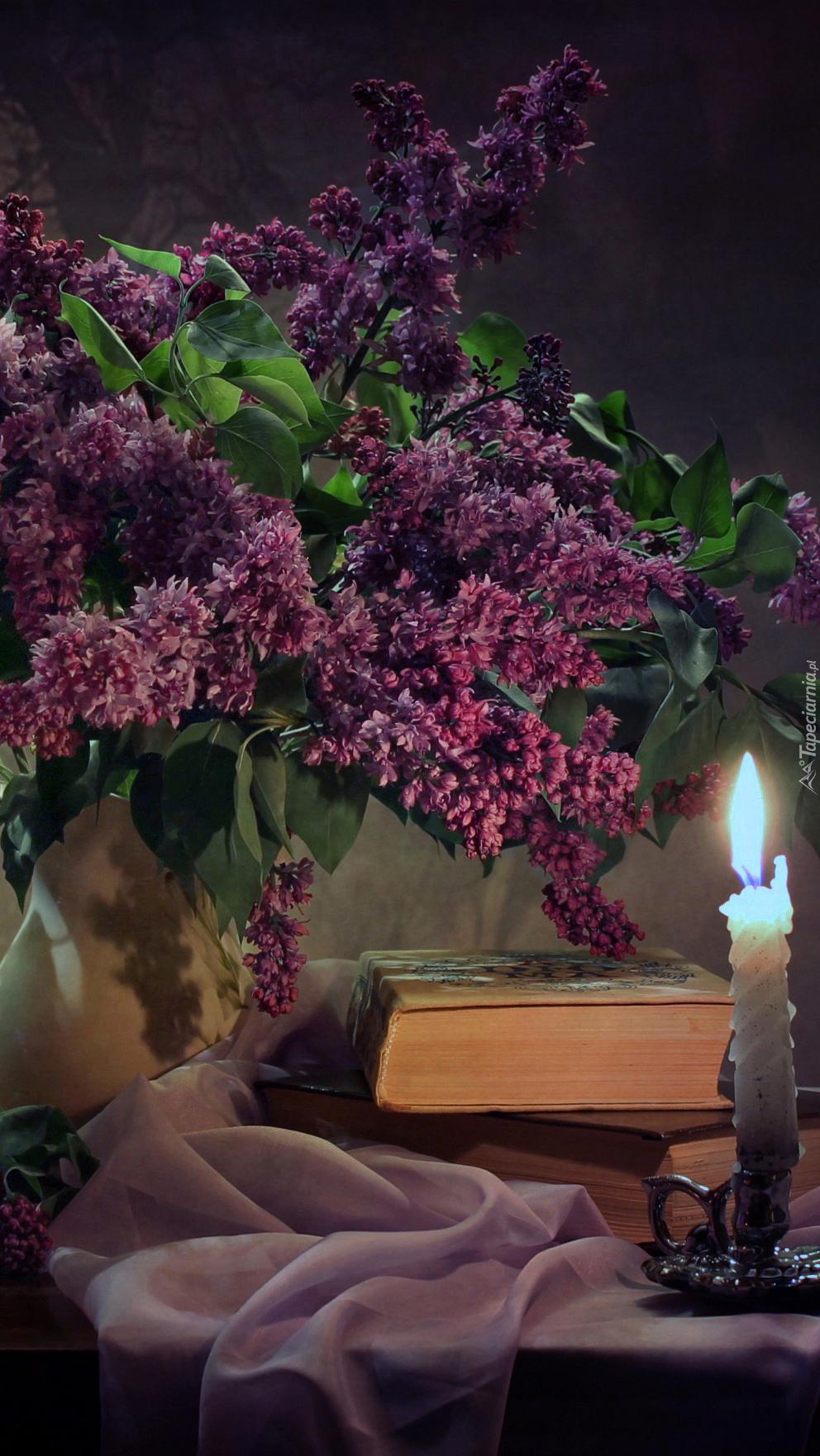 Kwiaty bzu obok książki i świecy na stole