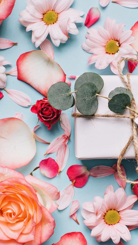 Kwiaty i płatki obok prezentu