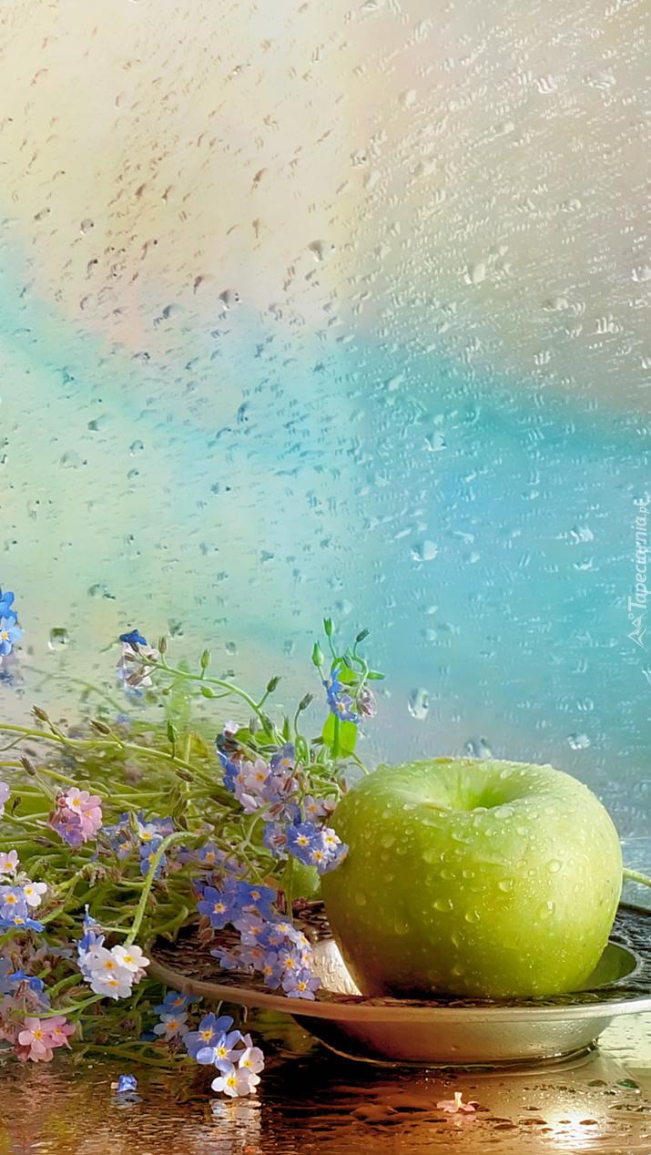 Kwiaty niezapominajki z jabłkiem w deszczu