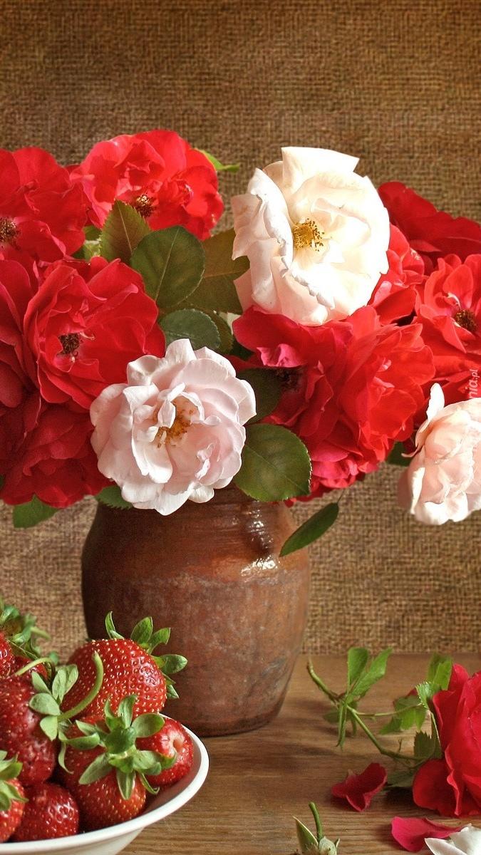 Kwiaty w wazonie i truskawki na talerzu