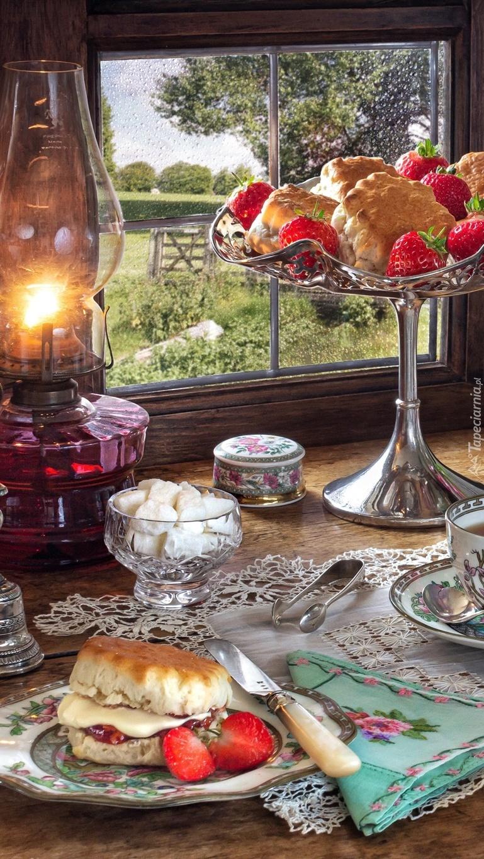 Lampa naftowa i patera z ciastem przy oknie