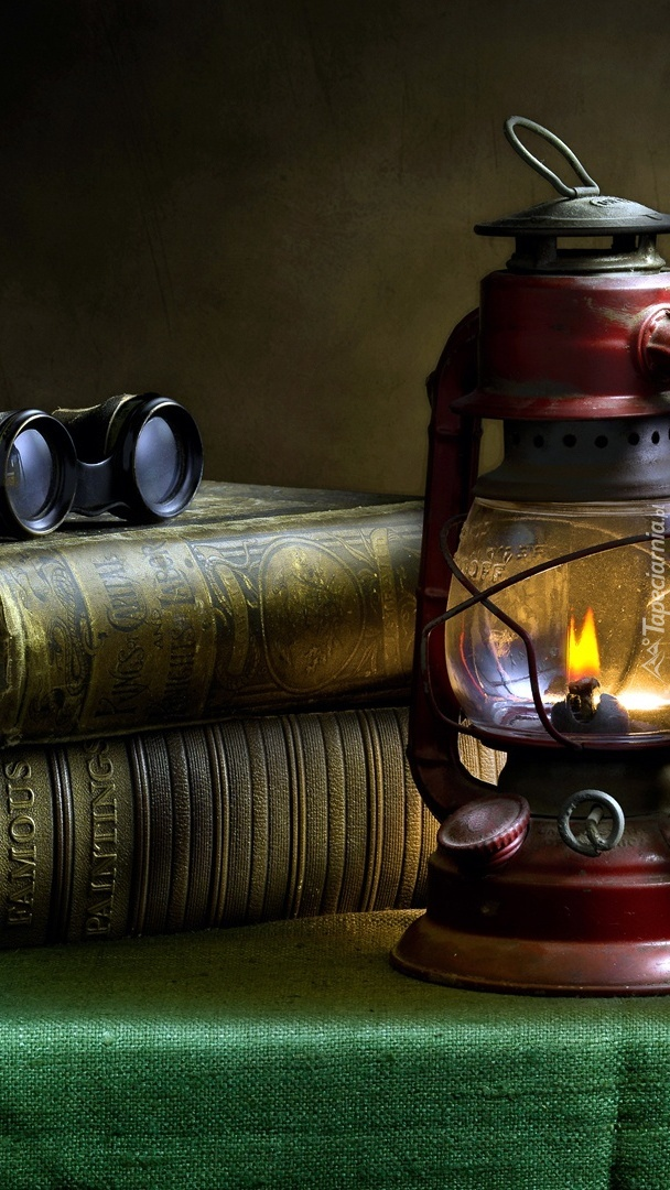 Lampa naftowa obok książek