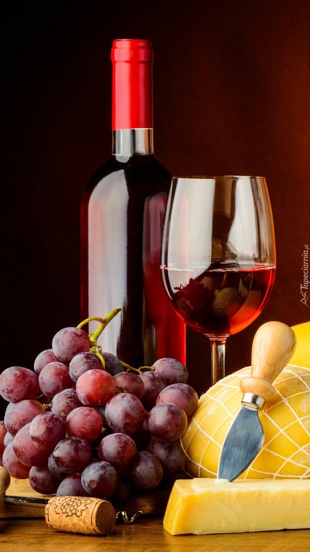 Lampka wina koło butelki i winogron